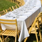 photo of table set with white cloth—2011 Outstanding in the Field Dinner—photo by The Farm Chicks