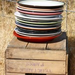photo of plates stacked on wooden crate—2011 Outstanding in the Field Dinner—photo by The Farm Chicks