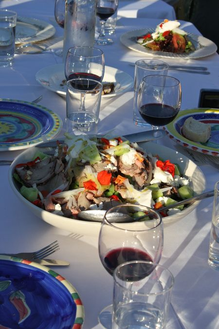 photo of salad and glasses of wine on table—2011 Outstanding in the Field Dinner—photo by The Farm Chicks