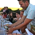 photo of server setting beautiful plate of grilled chicken on table—2011 Outstanding in the Field Dinner—photo by The Farm Chicks