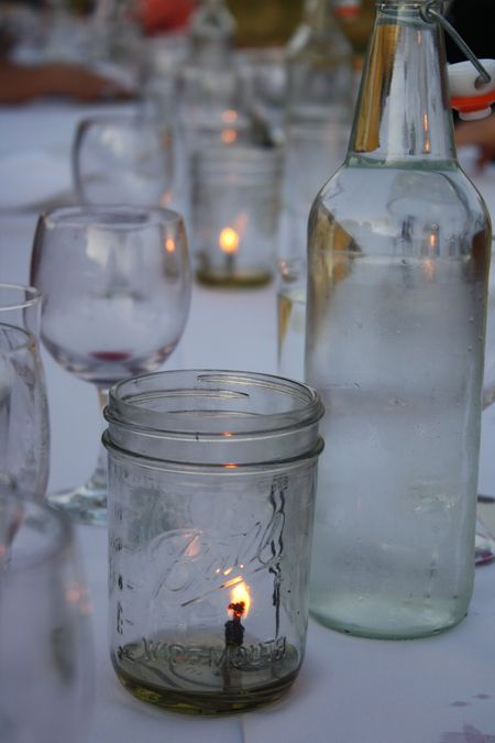 photo of lighted candle in a ball jar—2011 Outstanding in the Field Dinner—photo by The Farm Chicks