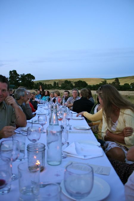 photo of people in conversation around the table—2011 Outstanding in the Field Dinner—photo by The Farm Chicks